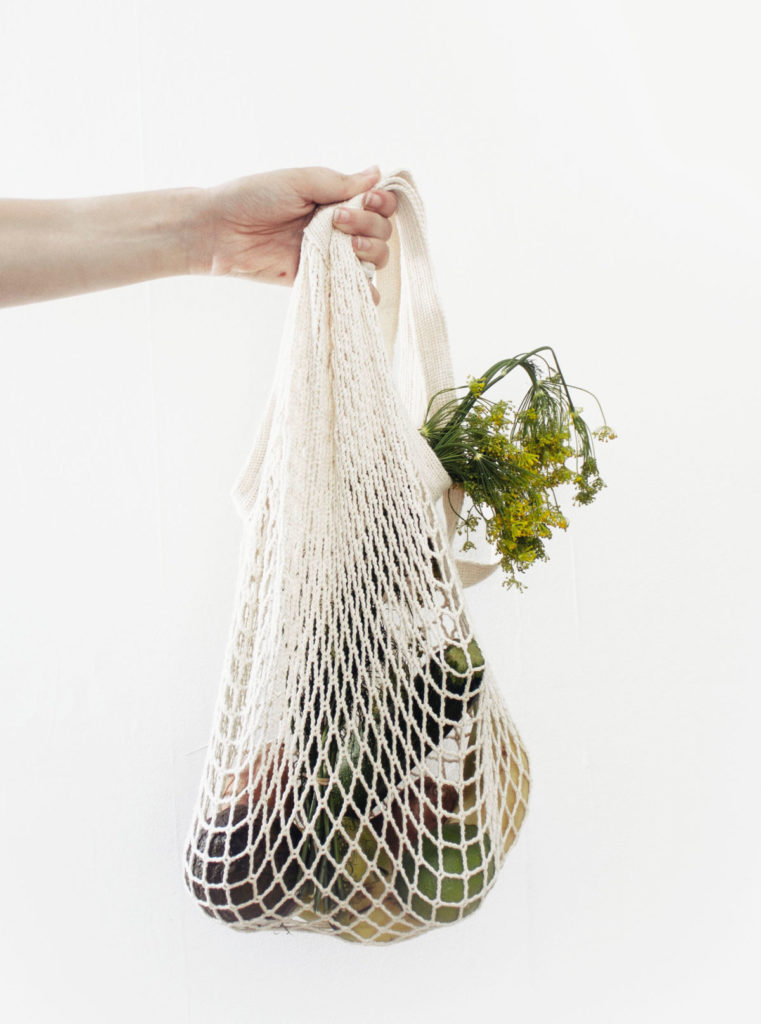 conscious consumer holding groceries in a weaved bag